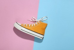 Yellow high-top sneaker (gumshoe) on pink blue bright background. Top view. Minimalism