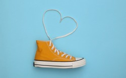 Yellow high-top sneaker (gumshoe) with untied heart shaped laces on blue background. Top view. Love concept