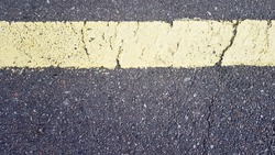 yellow horizontal strip on asphalt. Detail of a yellow stripe worn over time with a crack, road marking on asphalt.