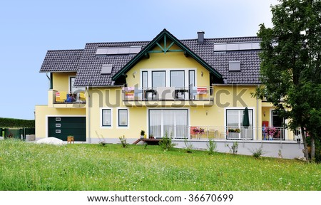 yellow house, green meadow, a tree, blue sky