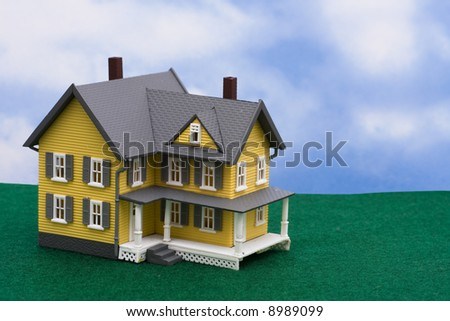 Yellow house on grass with sky background with copy space