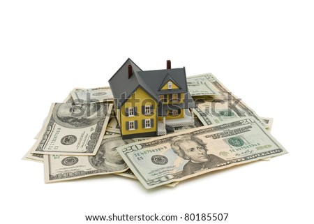 Yellow house on some American money isolated on white, Investing in a house
