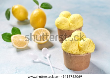 Yellow  ice cream in paper cup on on background in turquoise table, top view #1416752069