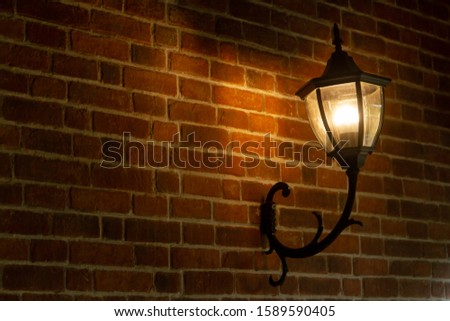yellow illuminated classic vintage lamp. attached on brick wall