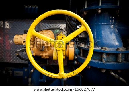 Yellow industrial valve in a large system