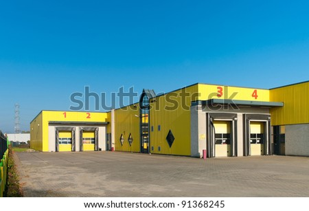 yellow industrial warehouse with numbered loading docks