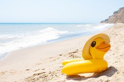 Yellow inflatable duck ring in summer straw hat laying on sandy empty beach near blue wavy ocean in sunny day. Protection swim tube for kid. Summer travel vacation resort concept. Copy space