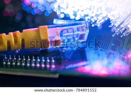 Yellow internet connection cable on circuit board, defocused optical fibre background. #784891552