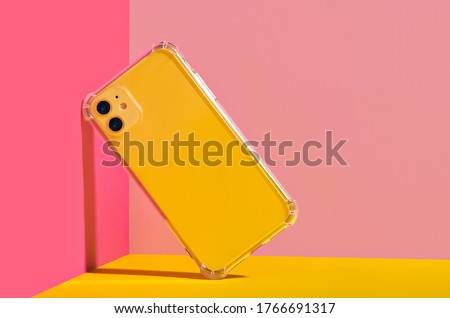 Photo of  Yellow iPhone 11 in clear phone case, bright and colorful phone case mock up