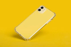 Yellow iPhone 11 in clear silicone case back view falling down isolated on a yellow background. Transparent phone case mock up
