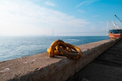 yellow iron ring rope mooring place on the pier in the background osmangazi bridge and ship