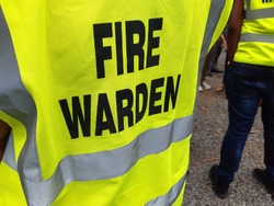 Yellow jacket showing fire warden on duty. Safety background.