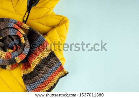 Yellow kids winter jacket composition on blue background. Flat lay, layout and tabletop mockup with copy space. Foto d'archivio ©