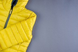Yellow kids winter jacket composition on yellow background. Flat lay, layout and tabletop mockup with copy space.