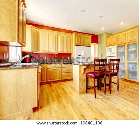 yellow kitchen with island and yellow wood with red and green colors