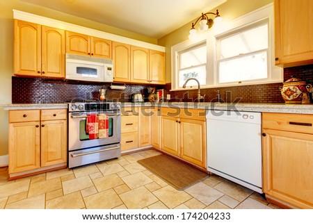 Yellow kitchen with wood cabinets and dark brown backsplash design ...