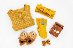 Yellow knitted romper, hairband, socks and cute baby slippers.  Set of newborn clothes and accessories. Flat lay, top view