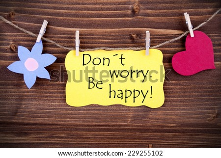 Yellow  Label Don't Worry Be Happy On Wooden Background With Two Symbols Like Heart And Flower