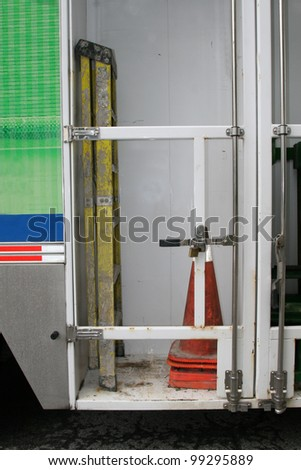 Yellow ladder and orange cone stored in truck - stock photo
