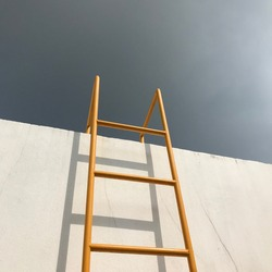 Yellow ladder, white wall and sky