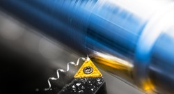 Yellow lathe tool bit detail working on metal product with reflection on shiny surface. Turning of silvery-blue workpiece with beautiful motion blur. Screwed swarf and white bokeh on black background.