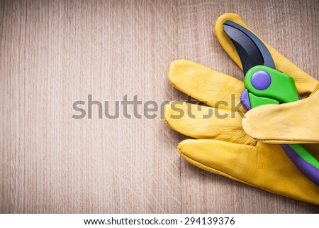 Yellow leather safety glove with secateurs on vintage board agricultural concept.