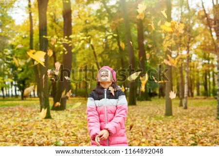 Yellow leaves falling on ecstatic child standing in autumn park and enjoying warm day