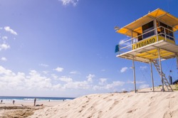 Yellow lifeguard tower watching over beach with blue sky at Snapper Rocks, Surfers Paradise, Queensland, Australia