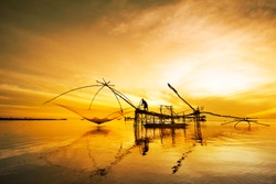 Yellow light of nature of Landscape photo in Thailand. Local asian and Thai fisherman use traditional net for fishing  longtime ago. In Asia fish menu is very popular and very cheap