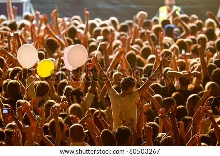 yellow lighted arded crowd at a live concert of a famous rockband