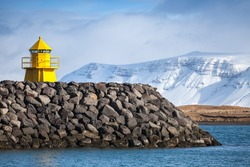 Yellow lighthouse tower on stone breakwater, entrance to Reykjavik port