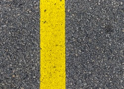 Yellow line. Band of yellow reflective paint on a black asphalt. Yellow line on road texture. Road marking.
