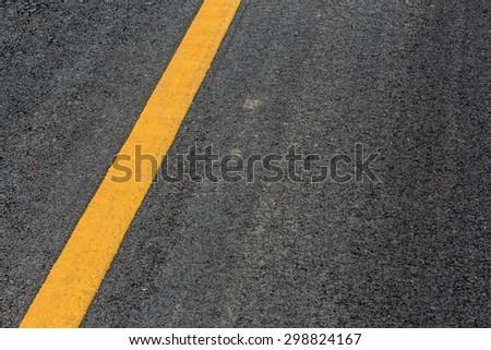 Yellow line on asphalt street road texture background