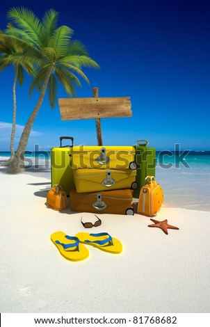 Yellow luggage, a blank wooden sign and thongs on a tropical beach