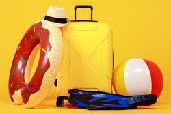 Yellow luggage with black handle, red and yellow beach ball, donut swim ring, blue flippers and hat against yellow background. Concept for beach and travel and vacation.
