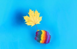 Yellow maple leaf. Through paper. Autumn mood. Autumn time. Man in colorful gloves hold maple leaf. Autumnal leaf. Falling leaves. Dry leaf. Isolated. Copy space. Sales. Discount.