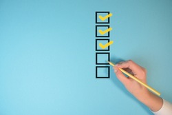 Yellow marking on checklist box isolated on blue background. Checklist concept. Hand holding a pencil and checklist isolated on pastel blue background with copy space.