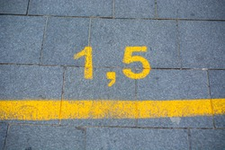Yellow marking on street in order to guide social distancing due to coronavirus or covid-19 pandemic. Yellow marking indicating how much distance people should keep to be safe. 1.5 meters, lockdown