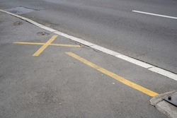 Yellow markings on the sidewalk, indicating a reserved parking space