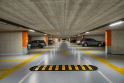 Yellow markings with blurred modern cars parked inside closed underground parking lot.