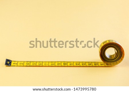 Yellow measuring tape on yellow background. Measuring tape for fitness. Close-up
