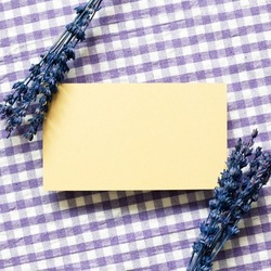 Yellow memo pad with purple lavender flowers on check pattern fabric background. top view, copy space