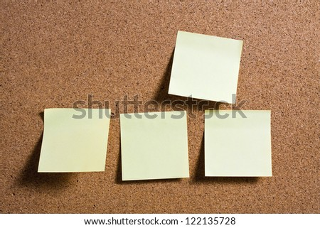 Yellow memo stick on cork board background