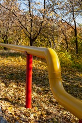 yellow metal gas supply pipe on red poles in an autumn park. The pipe makes a graceful bend in height