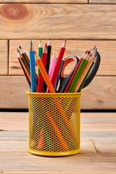 Yellow metal holder with multicolored pencils. Stationery supplies on wooden background. Concept of education.