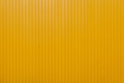 Yellow metal sheet panel or cladding with vertical line wave pattern.