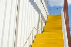 Yellow metal stairs with white corrugated wall, the hanging lights and the trees against the blue sky.