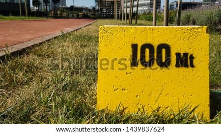 Yellow milestone showing 100 meters.