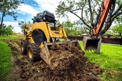 Yellow mini bulldozer working with earth, moving soil and doing landscaping works
