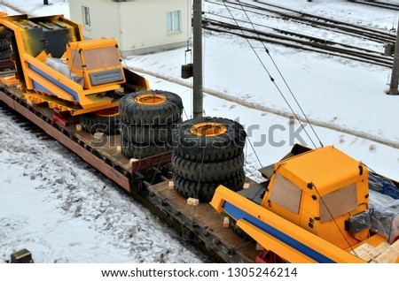 Yellow mining truck disassembled into parts, cab, body, electric motor, drive, wheels, loaded onto a cargo railway platform. Logistics of delivery of the truck, transportation of heavy heavy machinery